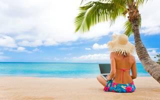 Chica con el ordenador portátil en la orilla arenosa